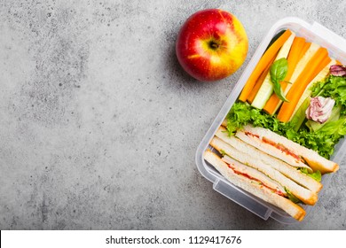 A lunchbox for office or school with healthy food: sandwiches, carrot and cucumber sticks, salad, apple. Preparation and packaging of meal to support balanced lifestyle, stone background, copy space