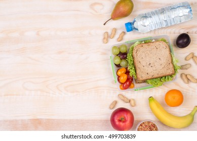 Lunchbox with sandwich, fruits, vegetables, and water, top view with copy space