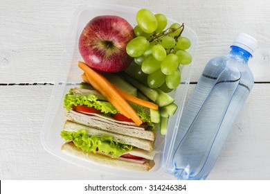 Lunchbox mit Sandwich, Gemüse und Obst, Flasche Wasser auf weißem Hintergrund
