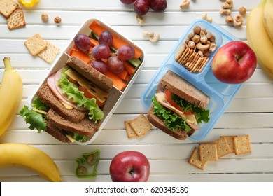 Lunchboxes with sandwiches and different products on wooden background