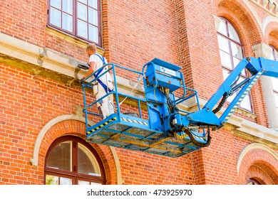 Lund, Sweden - August 24, 2016: Mason working with repairs on a building while standing in an aerial work platform or lift.