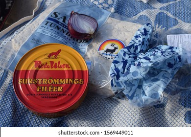 Lund, Sweden - September 26 2015: A can of Swedish fermented herring, called surstromming, sitting on a blanket with red onion and flat bread