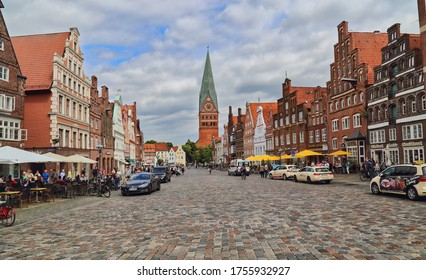Luneburg, Germany - July 4, 2019: Historical buildings and St. Johannis church tower and people walking on the Am Sande town square in the old center of Luneburg, Germany on July 4, 2019