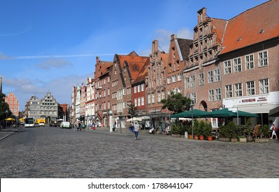 Luneburg, Germany - July 4, 2019: Am Sande town square with historical buildings and people walking in the old center of Luneburg, Germany on July 4, 2019