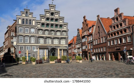 Luneburg, Germany - July 4, 2019: Historical buildings and people walking on the Am Sande town square in the old center of Luneburg, Germany on July 4, 2019