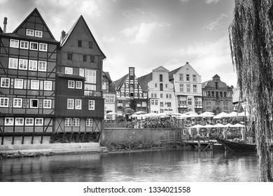 LUNEBURG, GERMANY - November 23, 2014: Historic old city and old harbour of Luneburg at evening with houses, water, cafe, umbrellas and boat