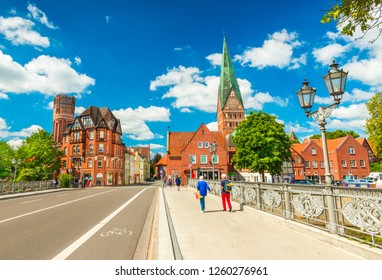 Luneburg - July 2018, Germany: Two women are walking on the bridge across the river. Cityscape of an old European city with traditional architecture