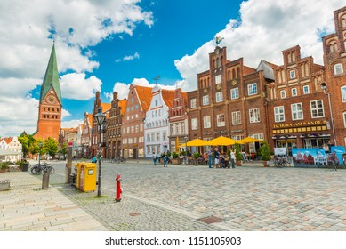 Luneburg - July 2018, Germany: View of the central street with old brick houses, bar, cafe, shops and walking people