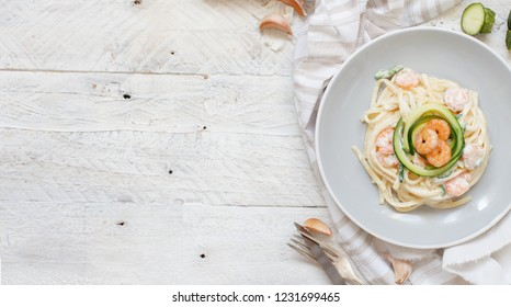 Lunguini with shrimps and zucchini with cream top view