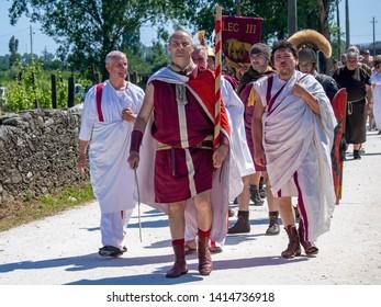 LUNI, MASSA CARRARA, ITALY – JUNE 2, 2019: Community event, Ancient Rome reenactment near Portus Lunae, genuine ancient settlement. Men in togas etc.