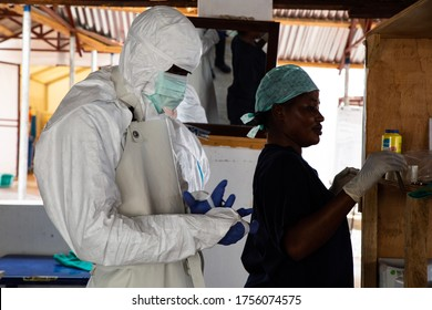 Lunsar, Sierra Leone - April 29,2015: a nurse and a medical worker prepared with safety equipment to enter dangerous zone of an ebola treatment center to check patients evolution. Pandemic context