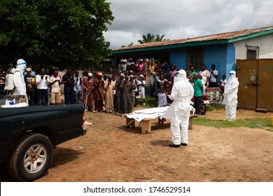 Lunsar, Sierra Leone - July 8, 2015: Burial team and family praying before taking the body away. ebola response epidemic disease in Africa, ebola and corona virus context