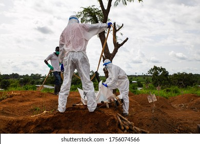 Lunsar, Sierra Leone - June 24, 2015: members of the burial team bury an ebola dead person in the main cemetery during pandemic. Ebola context