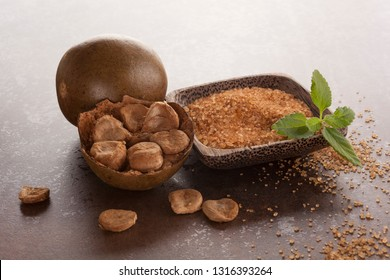 Luo Han Guo aka Monk fruit natural herbal remedy and sugar on brown background. Powerful healthy sweetener.