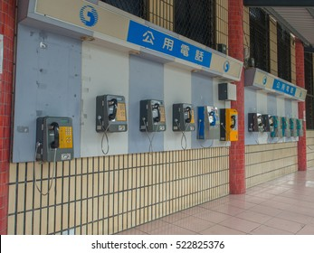 Luodong, Taiwan - October 18, 2016: More than a dozen of phones installed on the wall of a railway station building in Luodong