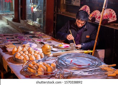 Luoyang, Henan Province / China - January 3, 2016: Man making and selling traditional handicrafts in Luoyang Old Town
