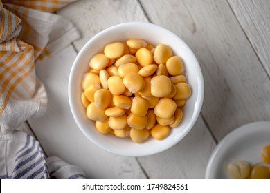 Lupins in a Bowl on a White Wooden Table with Napkins
