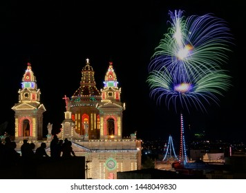 Luqa, Malta -7 jul,2019: Colorful amazing fireworks in Luqa, Malta with people sillouthes in the background,explode, Malta.Maltese fireworks.Pyrotechnics show