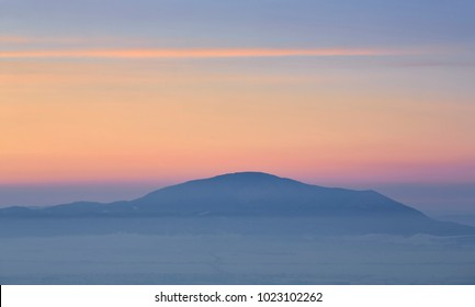 Lurid sunset over the Codlea Hillock silhouette in the misty valleys of Brasov county, Transylvania region, Romania.