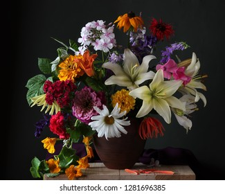 lush bouquet of garden flowers in a clay jug. lilies, Phlox, daisies and others.