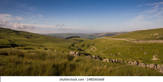 Lush grass pasture fills a limestone karst valley on the slopes of Pen-y-Ghent mountain in England's Yorkshire Dales National Park on a sunny day.