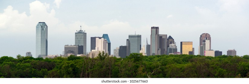 A lush green beltway appears in front of the urban landscape of Houston, TX USA