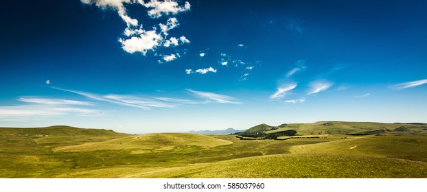 Lush green countryside and rolling hills, Auvergne, France in a panoramic landscape view under a sunny blue summer sky