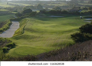 A lush green golf course bordered by a large sand bunker in late afternoon sunlight in southern California. One golf cart on the fairway.
