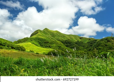 The lush green hills of Mount Schroeder and the white clouded blue skies over the island of Guam