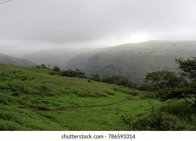 Lush green landscape and foggy mountains in Ayn Khor tourist resort, Salalah, Oman