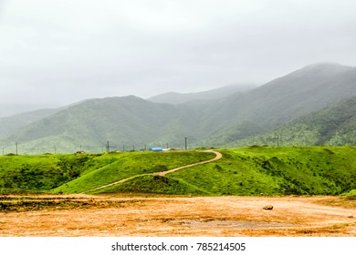Lush green landscape, trees and foggy mountains in Ayn Khor tourist resort, Salalah, Oman