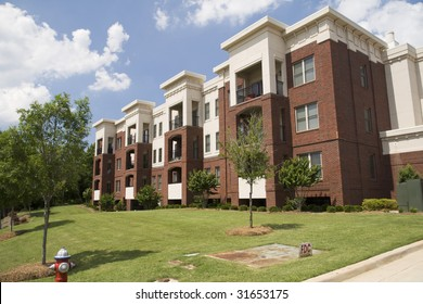 lush green lawn, tree form shrubs, and young trees beautify a brick and stucco apartment building