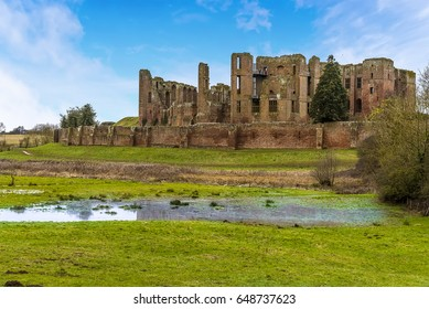 """The lush green meadow and small lake on the """"Great Mere"""", Kenilworth, UK looking towards the ruins of the Kenilworth castle on a bright winters day"""