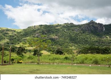 Lush, green, tropical rainforest under a blue sky with clouds in Nadi, Fiji/Uncultivated Fiji//Nadi, Fiji, Pacific Islands
