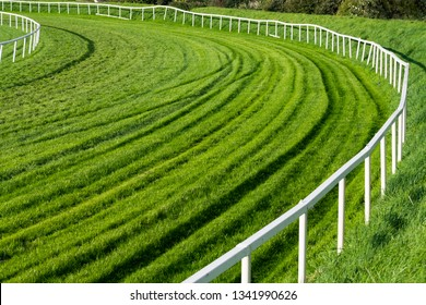 Lush green vibrant grass and railing bend on the turn of a race horse track