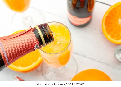Lush mix drinks, summer alcoholic beverages and refreshing brunch mimosa cocktail concept with top view of orange fruits and champagne pouring from bottle of bubbly isolated on wooden table background