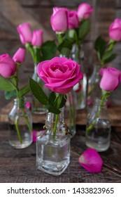 Lush pink roses in little vintage glass bottles