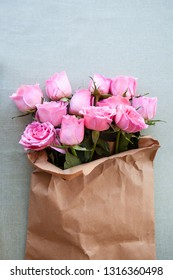 Lush pink roses in a rustic paper bag