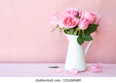 Lush pink roses in a vintage can on pink