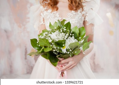 Lush wedding bouquet in the hands of the bride. A girl in a wedding dress holding a bouquet in a careless spring style