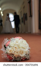 lush wedding bouquet red and beige colors is on the floor in the Museum in the background going into the distance the newlyweds