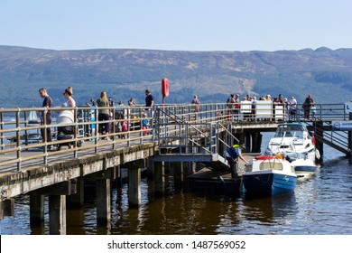 Luss, Argyll & Bute, Scotland, August, 25, 2019: Hundreds of people visit a small picturesque village on the west bank of Loch Lomond to sunbathe and have fun in water on very hot Sunday.