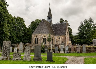 LUSS, SCOTLAND - AUGUST 1, 2019: Very old Luss Parish Church dedicated to Saint Kessog with a graveyard in front of it and grey sky