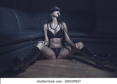 Lustful sexy dominatrix woman with whip sit on floor in lace eye cover, underwear latex platform boots, bdsm in nightclub