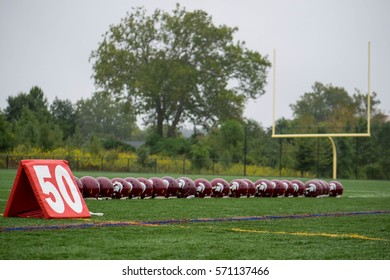 LUTHERVILLE, MARYLAND - October 1, 2016: Youth Football Helmets Lined Up on 50 Yard Line of FIeld