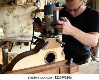 luthier carves a soundport guitar in a guitar.