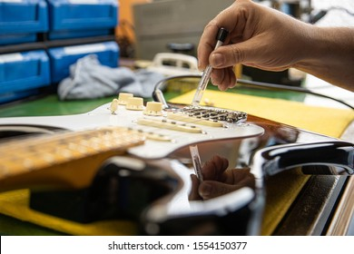 Luthier craftsman repairing an electric guitar, checking that the pads work