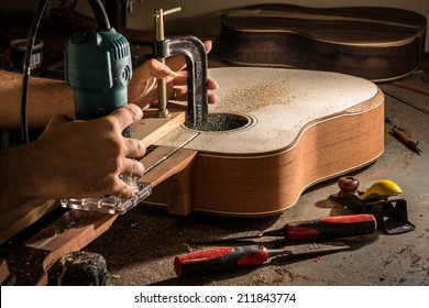 Luthier cutting a channel to place the truss rod in the guitar neck