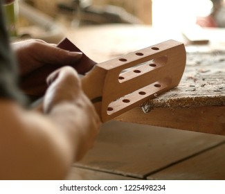 luthier grinds the head of the seven-string guitar.
