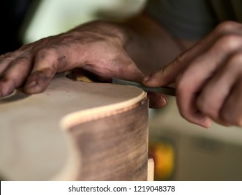 Luthier Install Binding on an guitar. Chamfering on the body of the guitar.